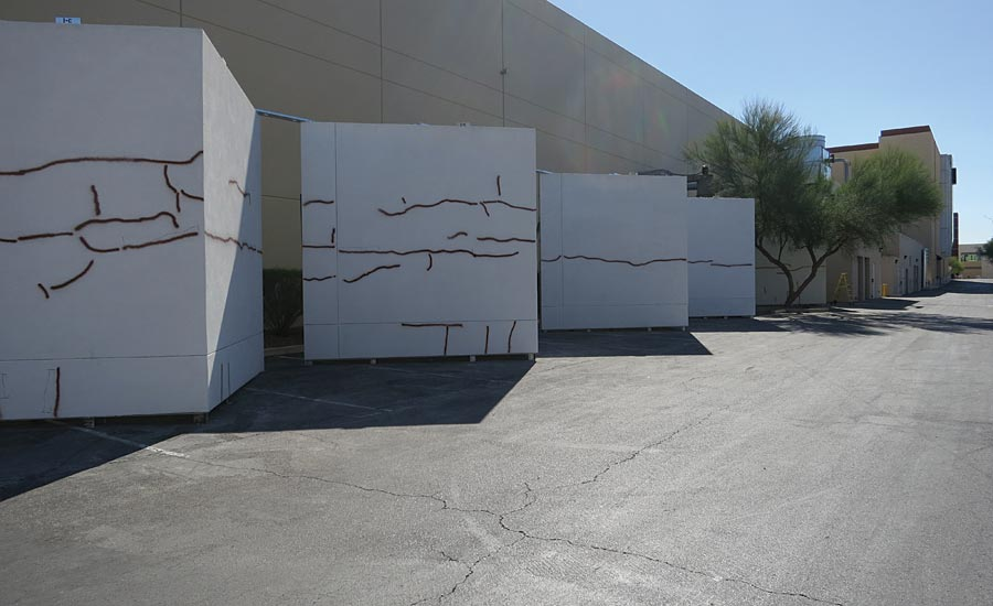 Five wall assemblies with cracks painted for visual location